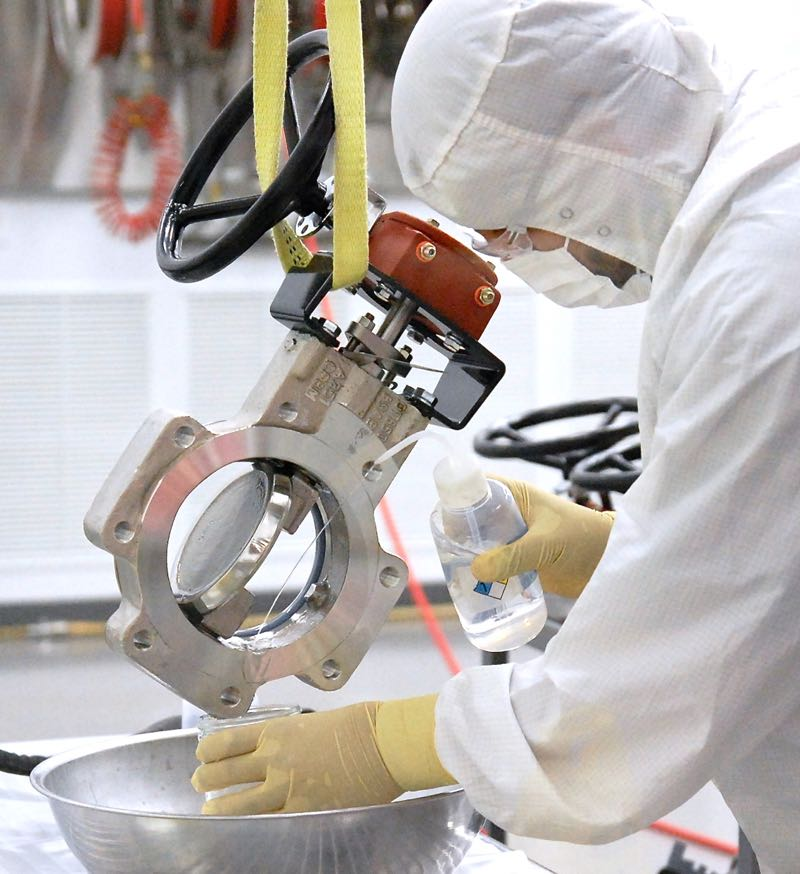 Astro pak employee cleaning inside cleanroom